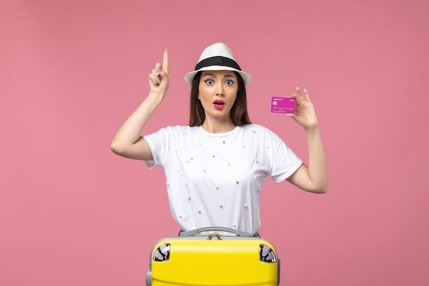 Vue de face jeune femme tenant une carte bancaire sur le voyage de femme d'argent de vacances de mur rose clair