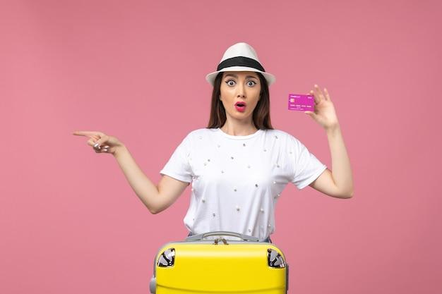 Vue de face jeune femme tenant une carte bancaire sur le voyage de femme d'argent de vacances de mur rose