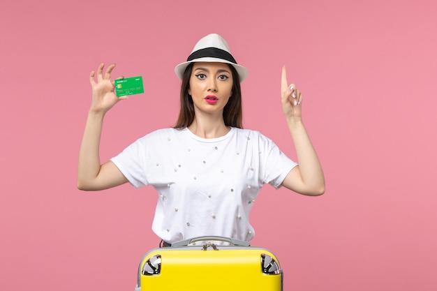 Vue de face jeune femme tenant une carte bancaire sur un voyage de femme d'été d'émotion de mur rose clair