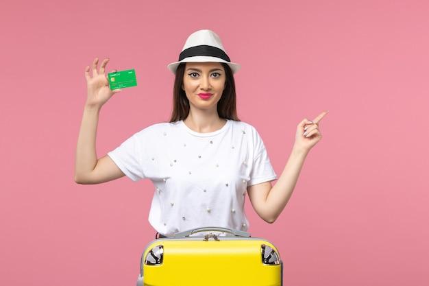 Vue de face jeune femme tenant une carte bancaire sur le voyage de femme d'été d'émotion de mur rose
