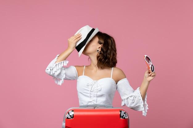 Vue de face d'une jeune femme tenant un chapeau et des lunettes de soleil avec un sac rouge sur le mur rose