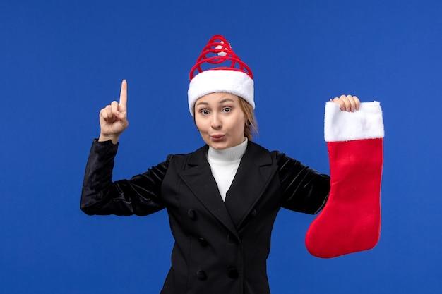 Vue de face jeune femme tenant chaussette de noël rouge sur le mur bleu vacances du nouvel an humain