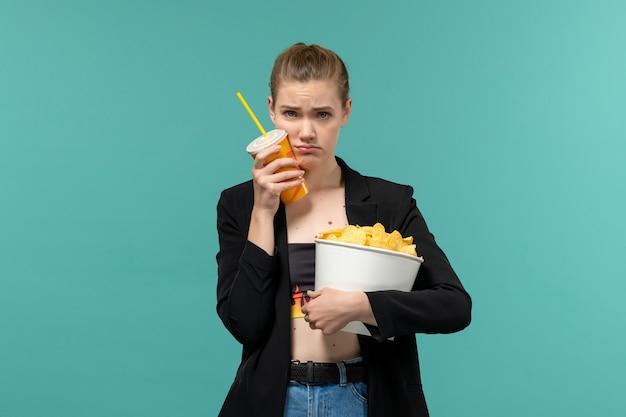 Vue de face jeune femme tenant des chips boire et regarder un film sur une surface bleu clair