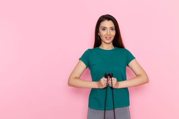 Vue de face jeune femme tenant la corde à sauter sur le mur rose exercice sport entraînement athlète taille beauté