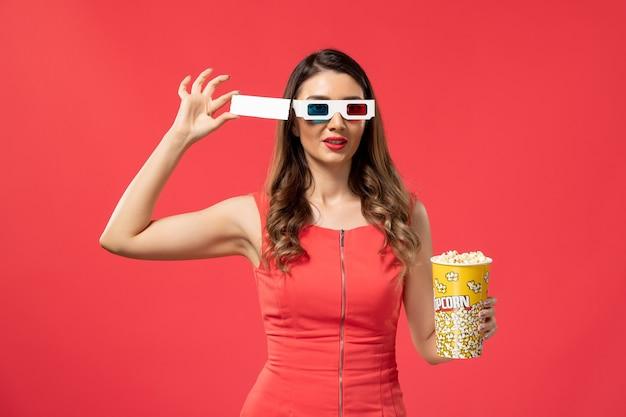 Vue de face jeune femme tenant du pop-corn avec billet en d lunettes de soleil sur un bureau rouge