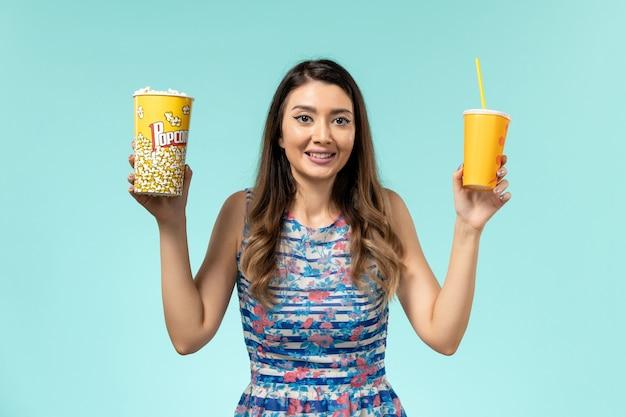 Vue de face jeune femme tenant du pop-corn et boire sur la surface bleu clair