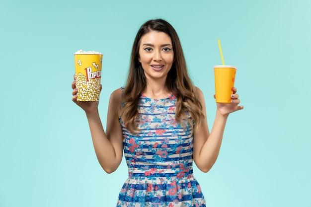 Vue de face jeune femme tenant du pop-corn et boire sur la surface bleue