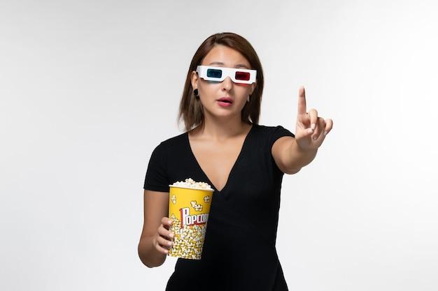 Vue de face jeune femme tenant du pop-corn dans des lunettes de soleil en regardant un film sur une surface blanche