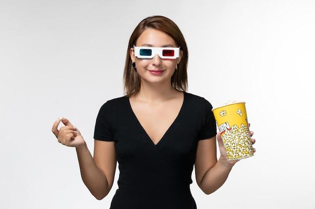 Vue de face jeune femme tenant du pop-corn et manger dans des lunettes de soleil en regardant un film sur une surface blanche