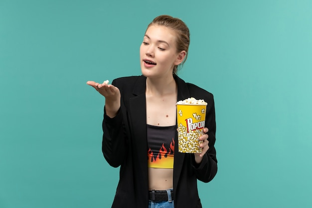 Vue de face jeune femme tenant du pop-corn et regarder un film sur un bureau bleu