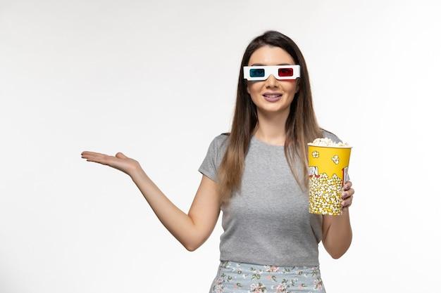 Vue de face jeune femme tenant du pop-corn et regarder un film dans des lunettes de soleil sur la surface blanche claire