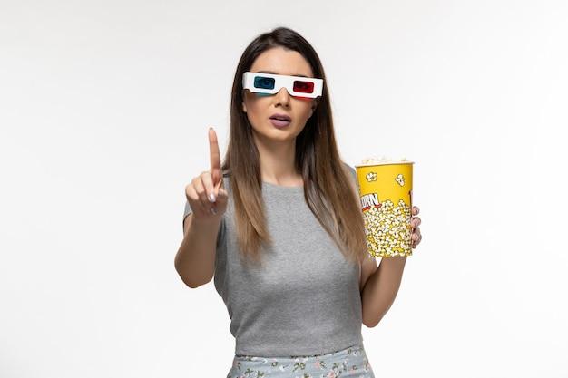 Vue de face jeune femme tenant du pop-corn et regarder un film dans des lunettes de soleil sur une surface blanche