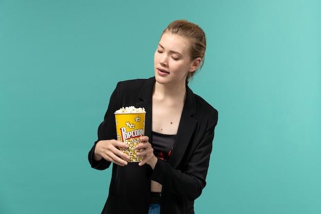 Vue de face jeune femme tenant du pop-corn et regarder un film sur la surface bleue