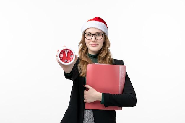 Vue de face jeune femme tenant des fichiers et de l'horloge sur le livre de noël du nouvel an plancher blanc