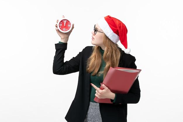 Vue de face jeune femme tenant des fichiers et de l'horloge sur le mur blanc livre leçon college