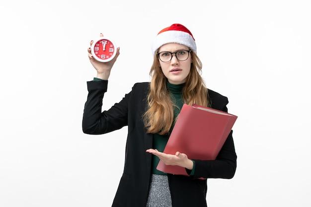 Vue de face jeune femme tenant des fichiers et horloge sur mur blanc livre leçons college