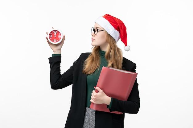 Vue de face jeune femme tenant des fichiers et horloge sur mur blanc livre de noël du nouvel an