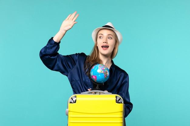 Vue de face jeune femme tenant le globe et la préparation pour les vacances sur le fond bleu avion vacances voyage voyage mer