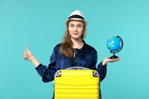 Vue de face jeune femme tenant le globe et la préparation pour les vacances sur fond bleu avion voyage de vacances femme voyage