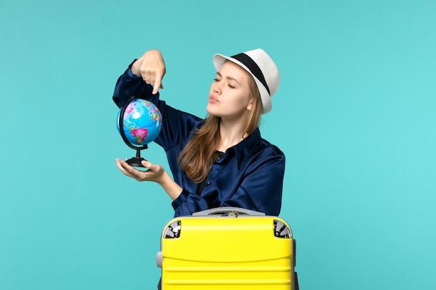 Vue de face jeune femme tenant le globe et la préparation pour les vacances sur fond bleu clair voyage féminin vacances en avion de mer