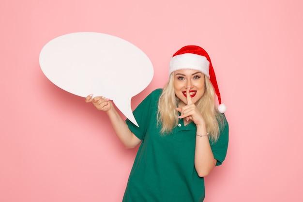 Vue de face jeune femme tenant grand panneau blanc sur le mur rose femme photo couleur neige vacances de nouvel an