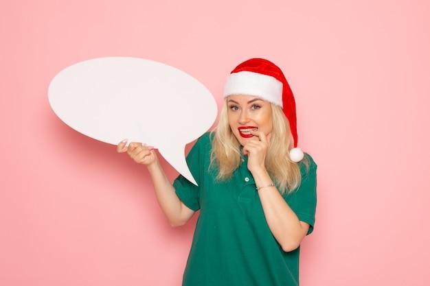 Vue de face jeune femme tenant grand panneau blanc sur mur rose photo femme neige vacances nouvel an