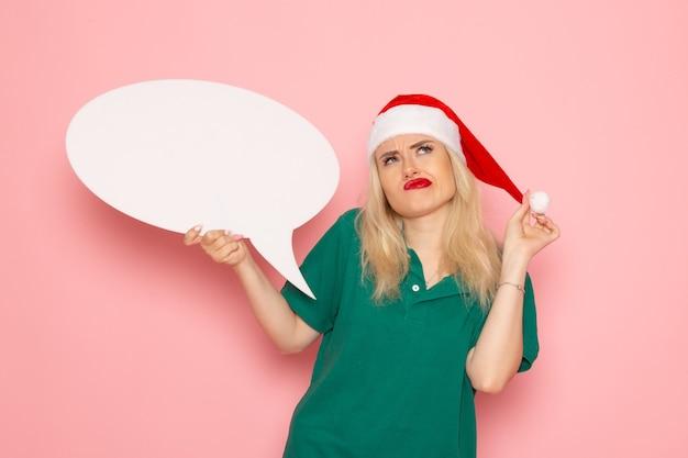 Vue de face jeune femme tenant grand panneau blanc pensant sur le mur rose femme photo couleur neige vacances nouvel an