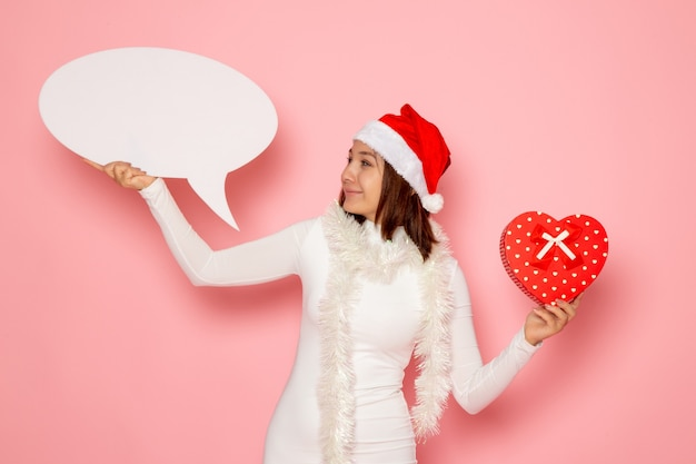 Vue de face jeune femme tenant grand panneau blanc et présent sur la couleur du mur rose