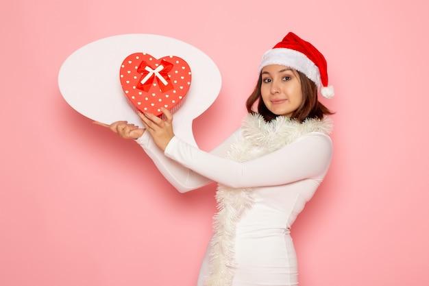 Vue de face jeune femme tenant grand panneau blanc et présent sur les émotions de mur rose couleur neige noël nouvel an vacances