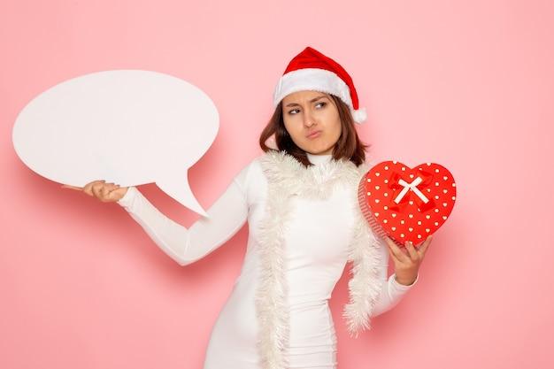Vue de face jeune femme tenant grand panneau blanc et présent sur le mur rose couleur émotion neige noël vacances nouvel an