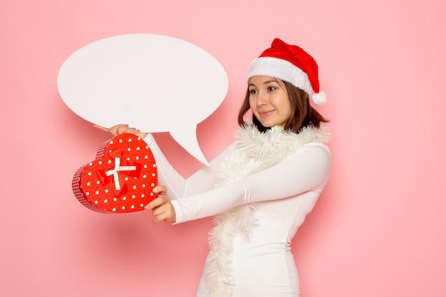 Vue de face jeune femme tenant grand panneau blanc et présent sur le mur rose couleur émotion neige vacances nouvel an