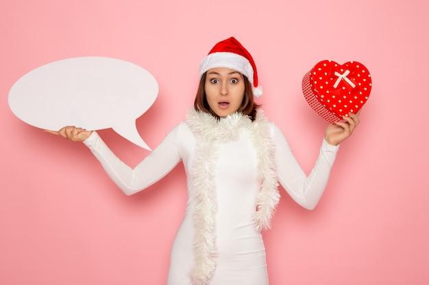 Vue de face jeune femme tenant grand panneau blanc et présent sur le mur rose couleur neige noël nouvel an vacances d'émotion