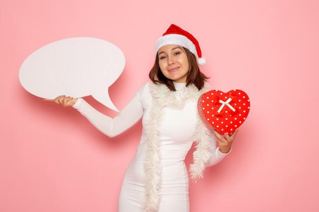 Vue de face jeune femme tenant grand panneau blanc et présent sur le mur rose neige noël nouvel an vacances d'émotion