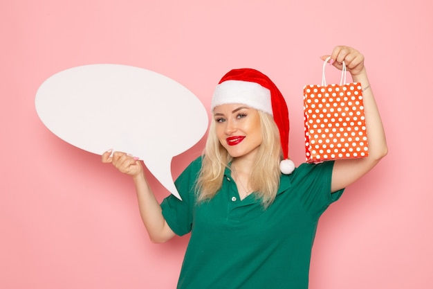 Vue de face jeune femme tenant grand panneau blanc et présent sur le mur rose photo couleur neige nouvel an vacances femme