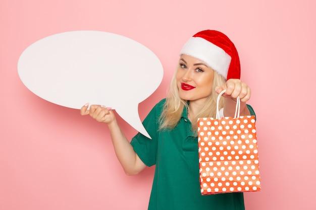 Vue de face jeune femme tenant grand panneau blanc et présent sur le mur rose photo couleur neige vacances nouvel an femme