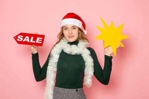 Vue de face jeune femme tenant grande figure jaune et vente écrit sur la couleur du mur rose clair vacances noël nouvel an émotion