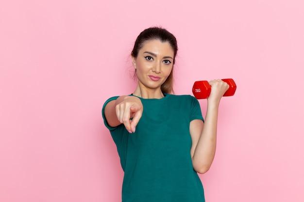 Vue de face jeune femme tenant des haltères sur les athlètes de mur rose sport exercice exercices de santé