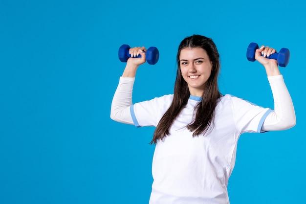 Vue de face jeune femme tenant des haltères bleus sur mur bleu