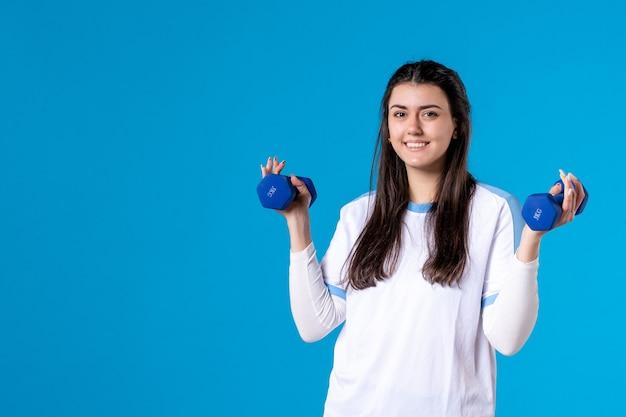 Vue de face jeune femme tenant des haltères bleus