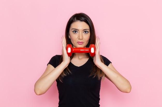 Vue de face jeune femme tenant des haltères sur le bureau rose clair athlète sport exercice santé entraînement