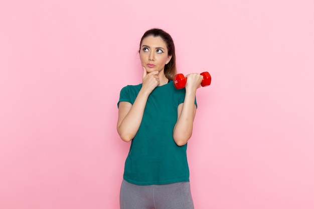 Vue de face jeune femme tenant des haltères sur le mur rose athlète sport exercice santé entraînements