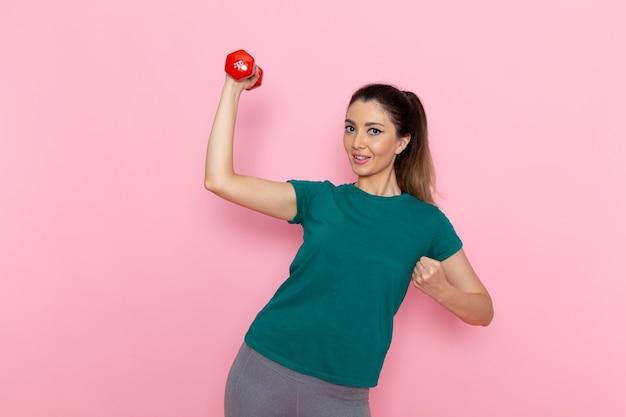 Vue de face jeune femme tenant des haltères et souriant sur les séances d'entraînement de santé exercice sport athlète mur rose