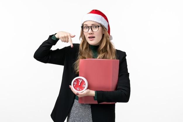 Vue de face jeune femme tenant horloge et fichiers sur la leçon de livre du collège étage blanc