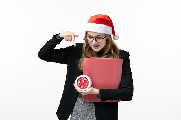 Vue de face jeune femme tenant horloge et fichiers sur leçon de livre d'université de bureau blanc