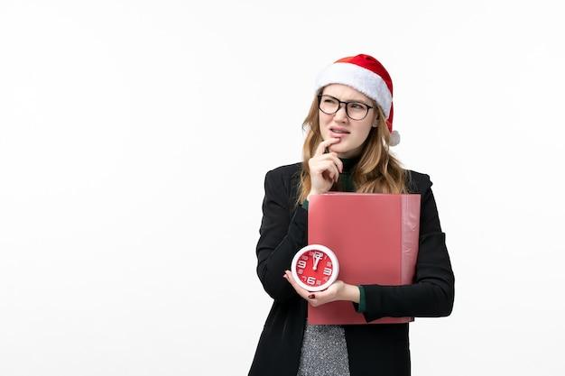 Vue de face jeune femme tenant horloge et fichiers sur les leçons de livre d'université de mur blanc