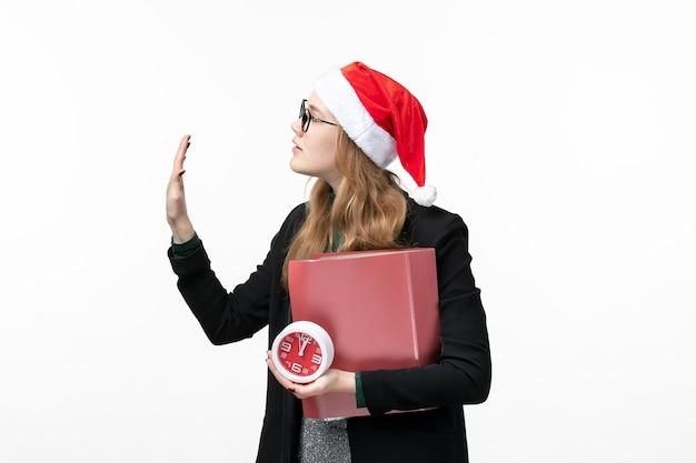Vue de face jeune femme tenant horloge et fichiers sur livre de collège de leçon de bureau blanc