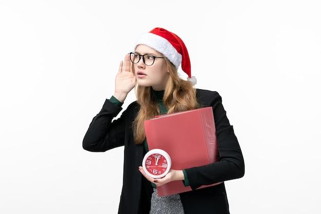Vue de face jeune femme tenant une horloge et des fichiers sur le livre d'université de leçon de mur blanc