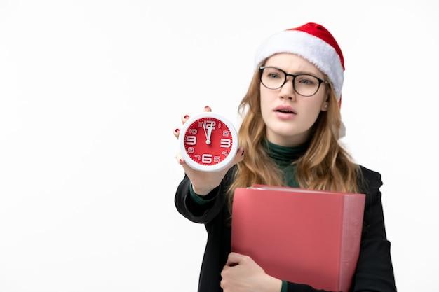 Vue de face jeune femme tenant horloge avec des fichiers sur le livre de l'université de leçon de mur blanc