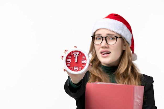 Vue de face jeune femme tenant horloge avec des fichiers sur le livre de l'université de leçon de plancher blanc