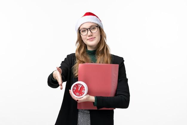 Vue de face jeune femme tenant une horloge et des fichiers sur le mur blanc leçon de livre d'université